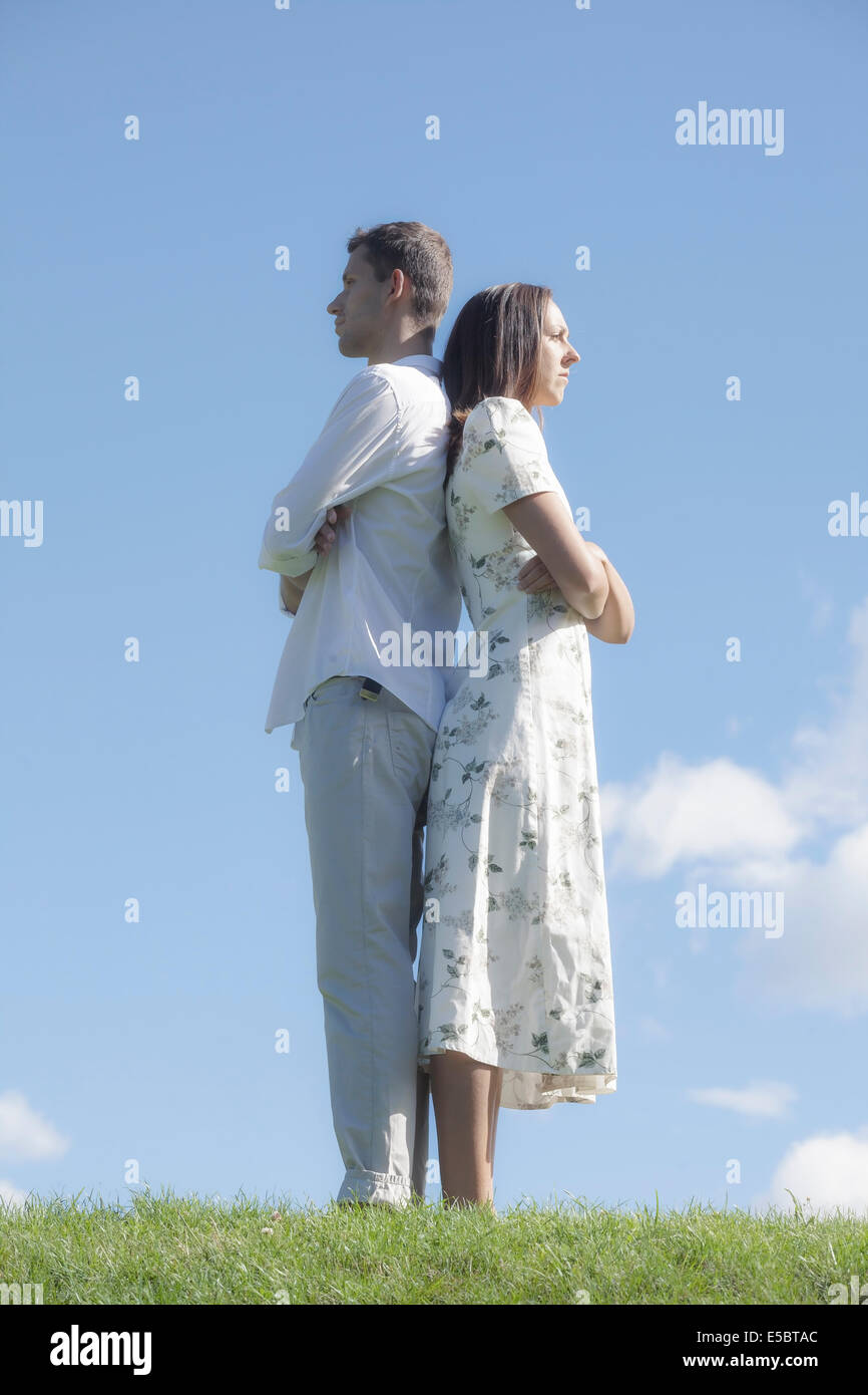 a couple back to back on a meadow - Stock Image