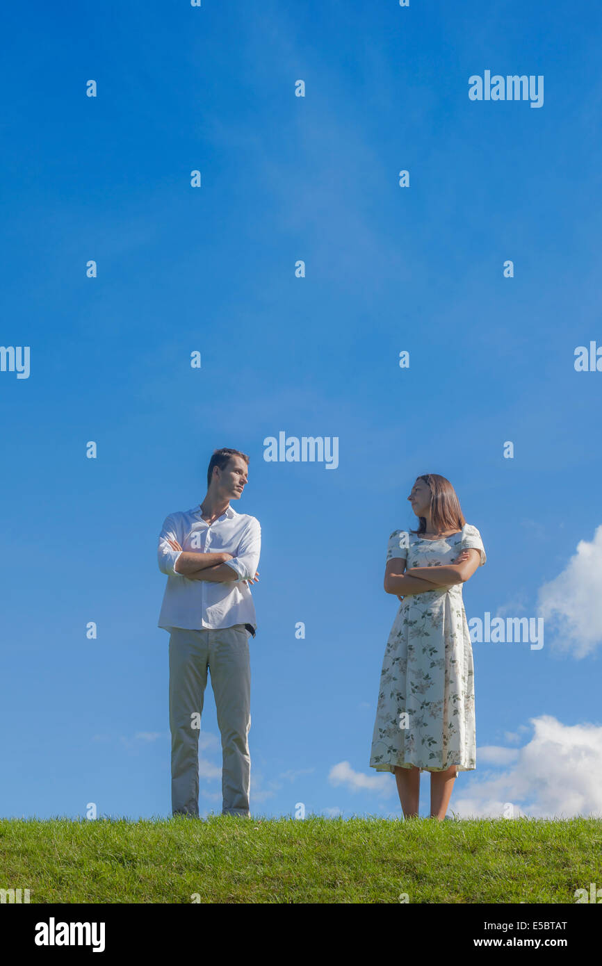 a couple with a conflict on a meadow - Stock Image