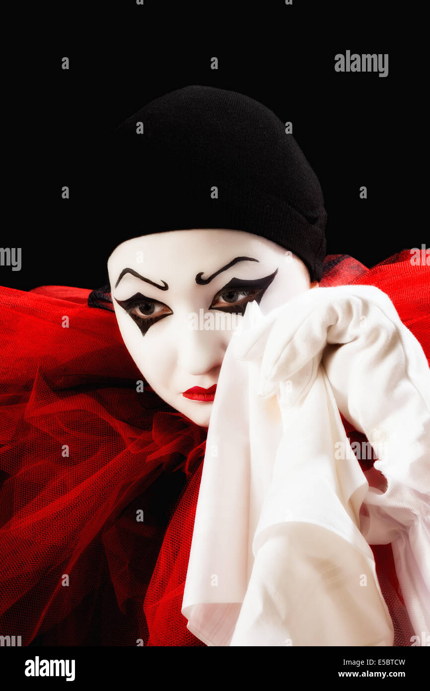 Mime actor dressed as Pierrot crying with a hanky - Stock Image