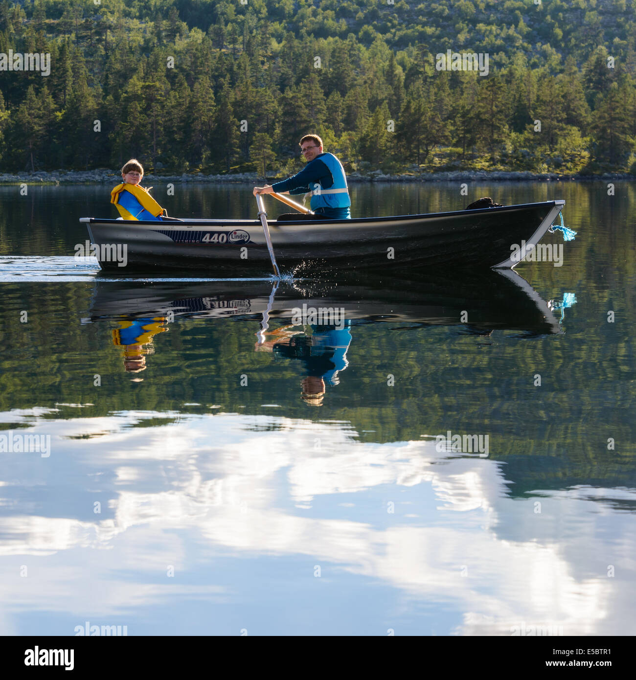 Two people rowing a small boat on lake, Dalarna Stock Photo