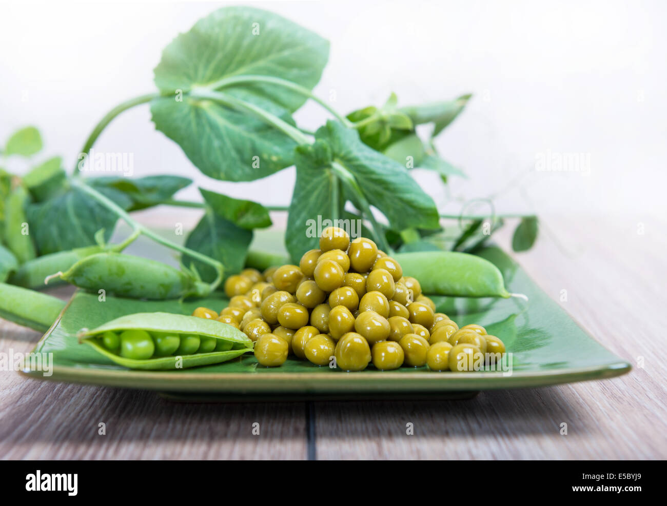 Boiled green peas on a platter, pods and branches Stock Photo