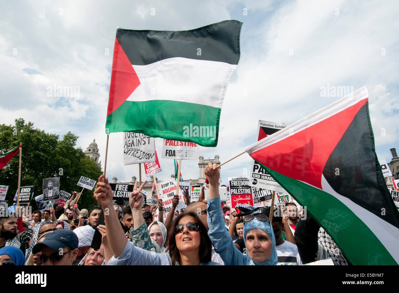 Demonstration against Israeli bombing of Gaza,  Protesters listen to speeches and wave Palestinian flags in Parliament - Stock Image