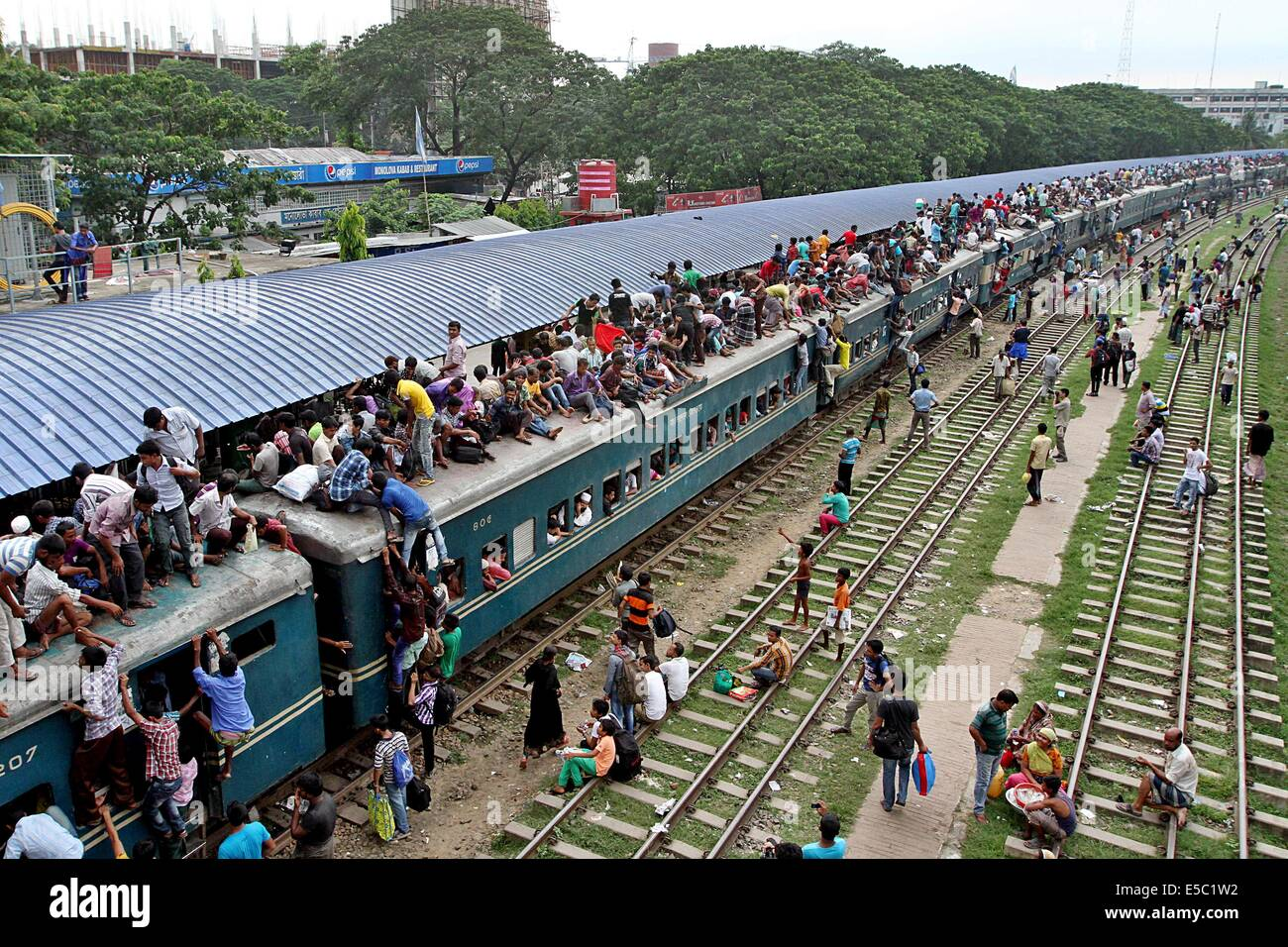 Dhaka, Bangladesh. 26th July 2014 -- A train leaves Dhaka with crammed compartments and no room left on its roof. Stock Photo