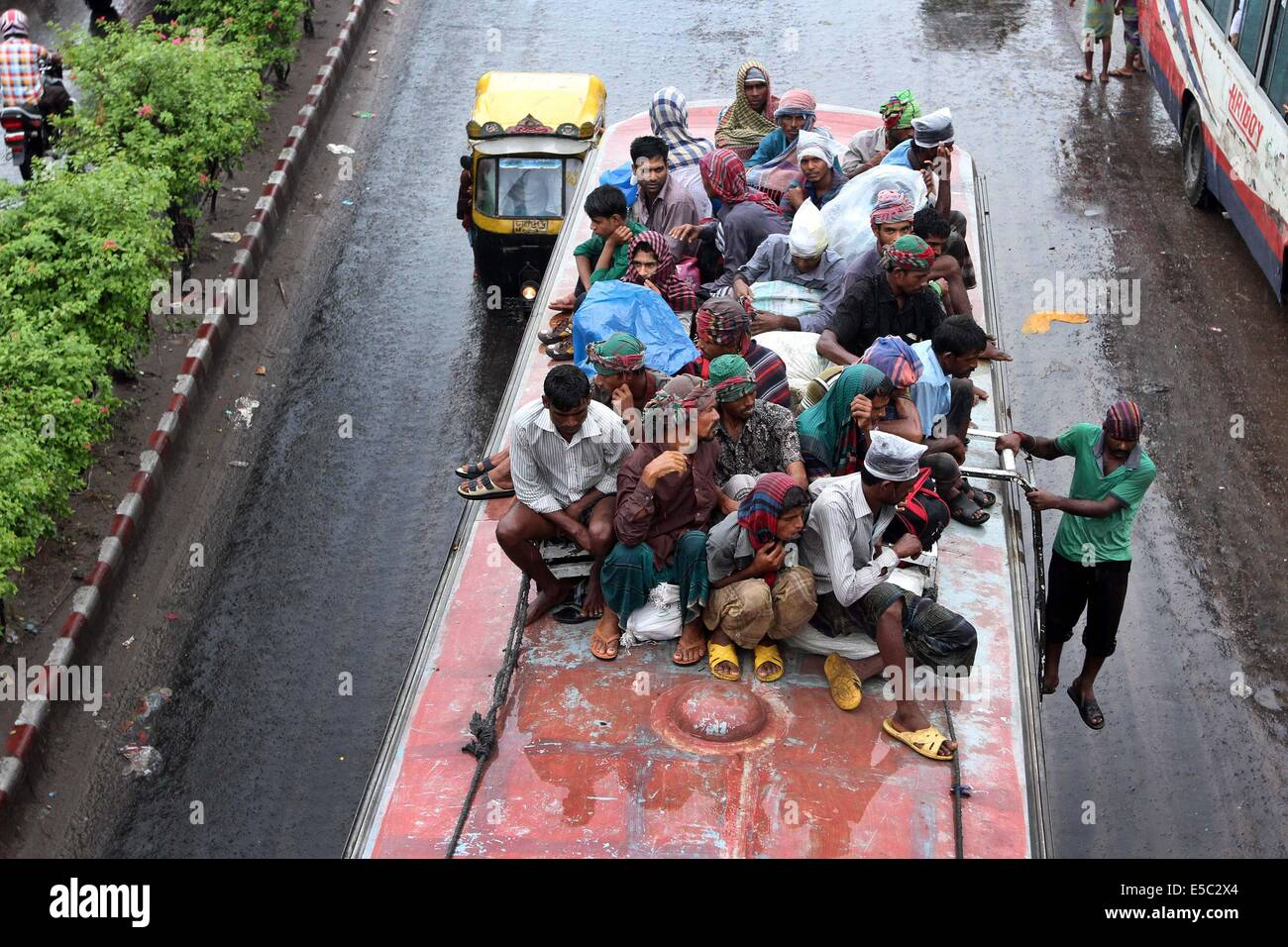 Dhaka, Bangladesh. 27th July 2014 People stay on the rooftop of a homebound bus in Dhaka, capital of Bangladesh. - Stock Image