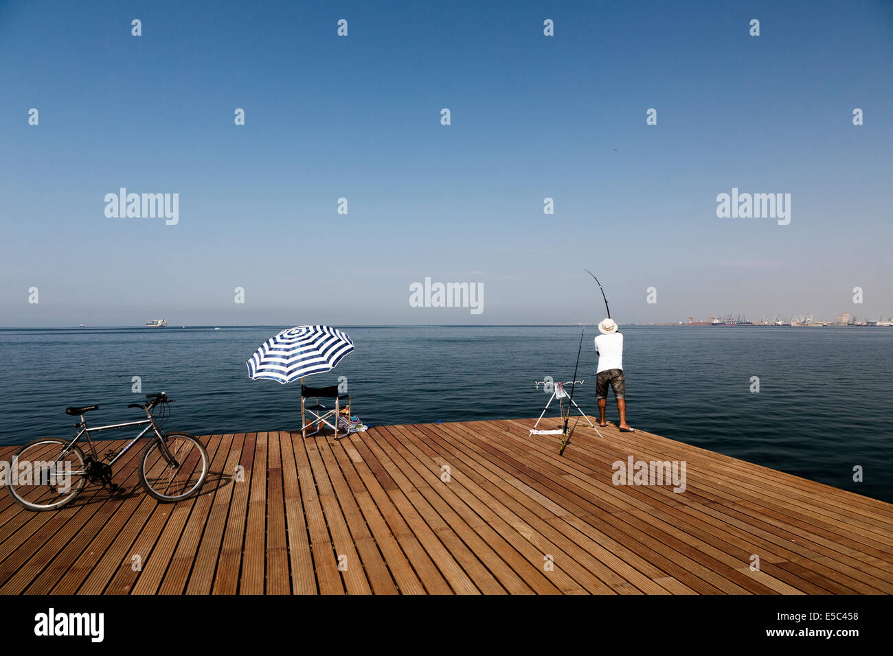A fisher cast his line at the seafront of Thessaloniki, Greece. - Stock Image