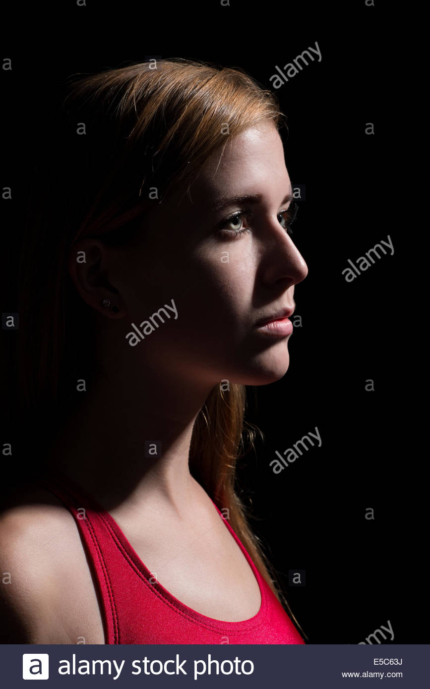teen girl in red bathing suit on a black background - Stock Image