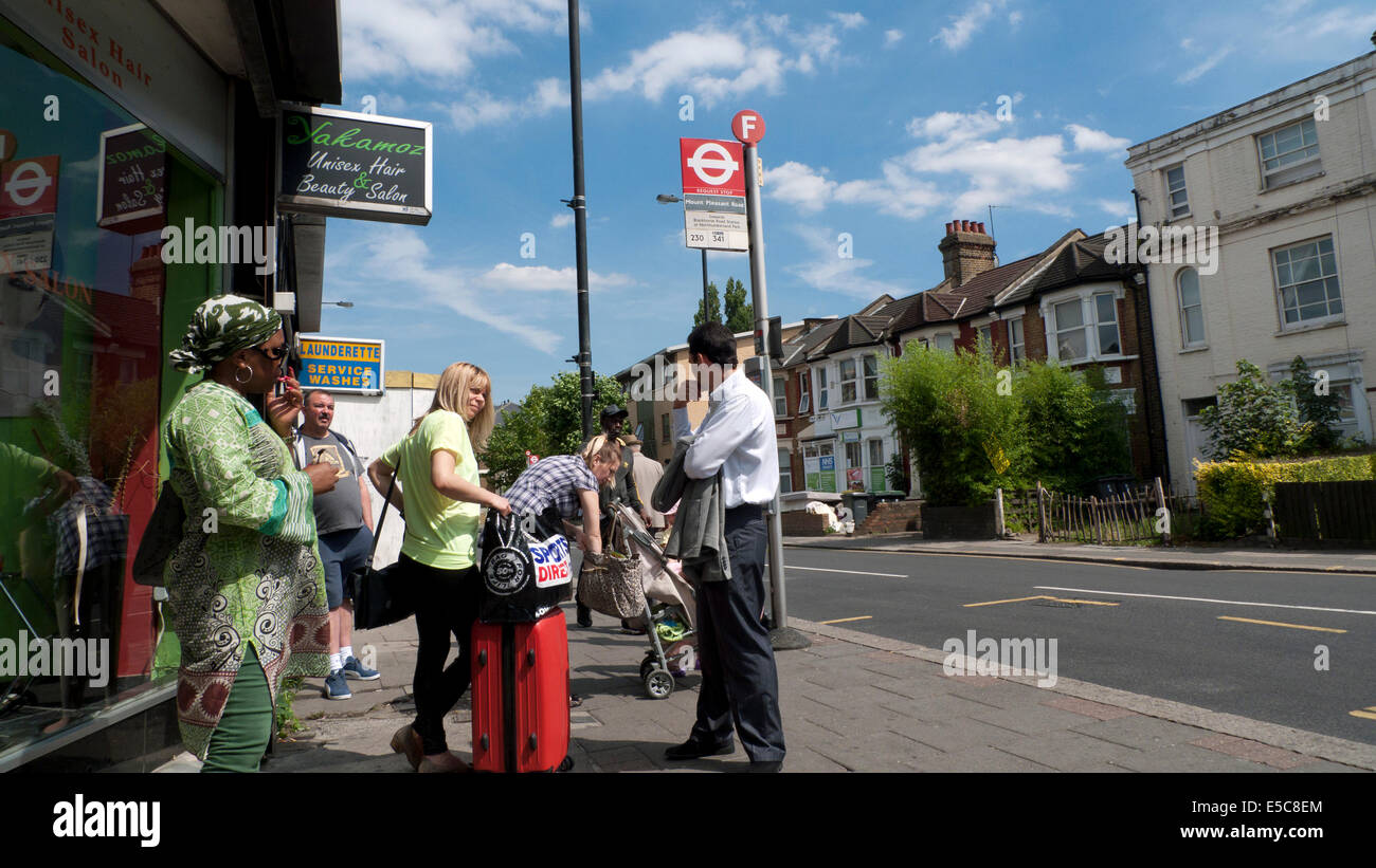 People waiting for a bus at a Philip Lane bus stop in summer Tottenham, London N15 England UK  KATHY DEWITT - Stock Image