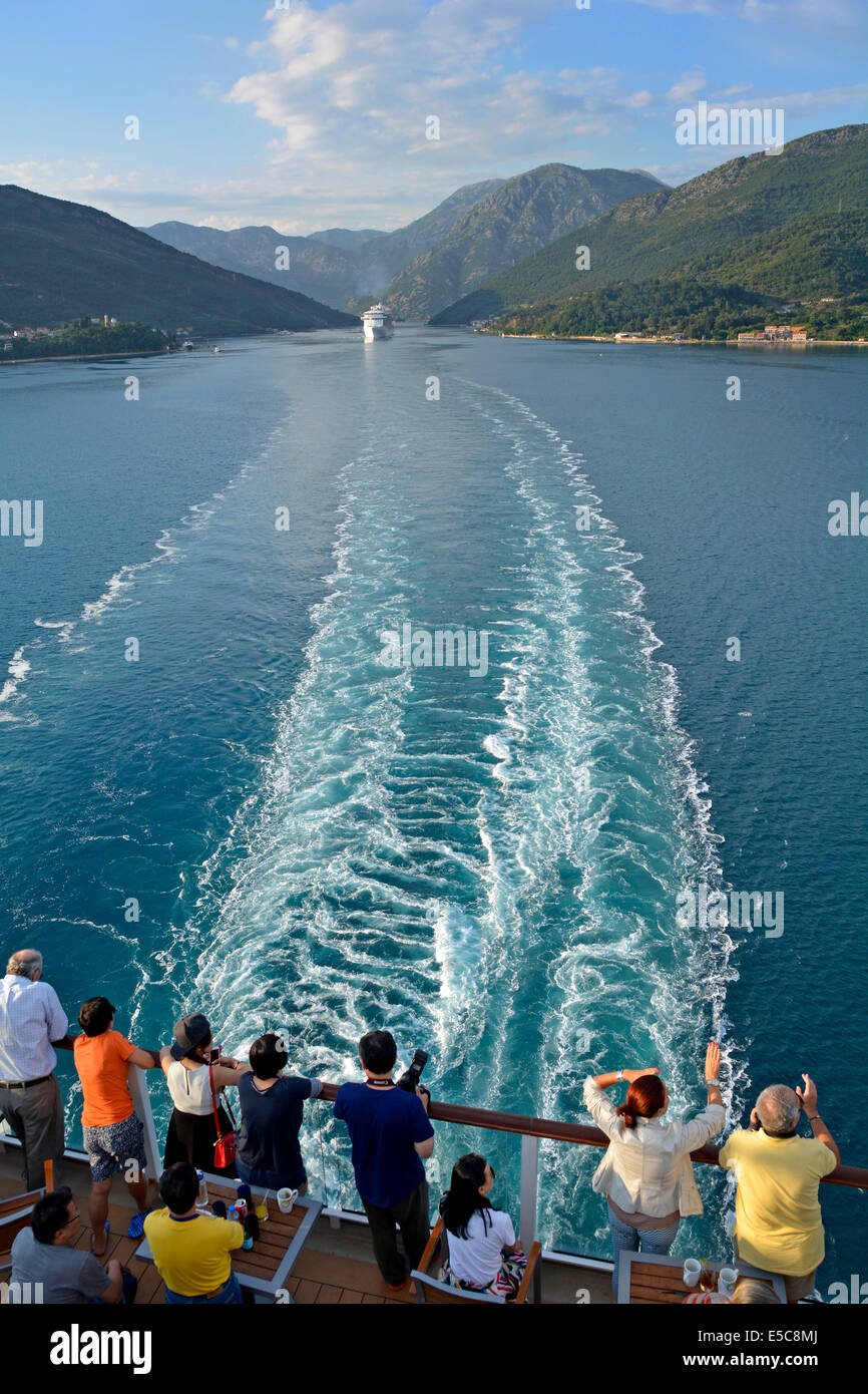 Passengers and stern wake of cruise ship departing the Verige Strait in Kotor Bay with another cruise liner following - Stock Image