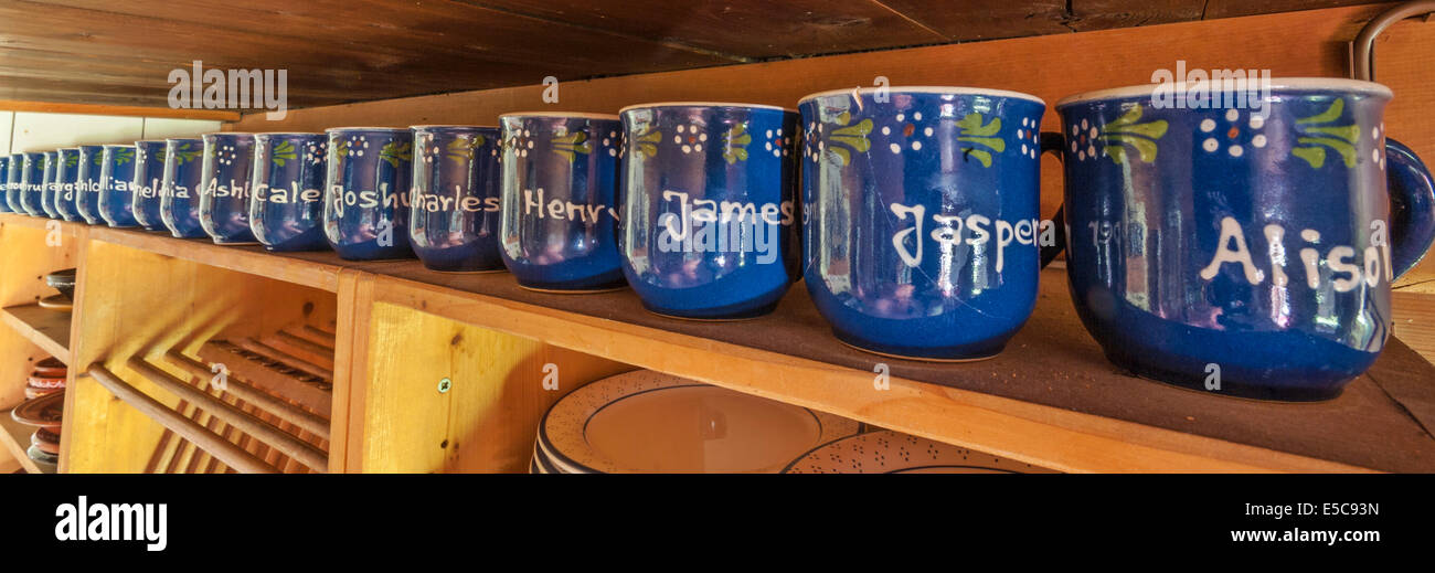 A row of named mugs on the shelf of the kitchen in a Swiss farmhouse, from an extended farming family. - Stock Image