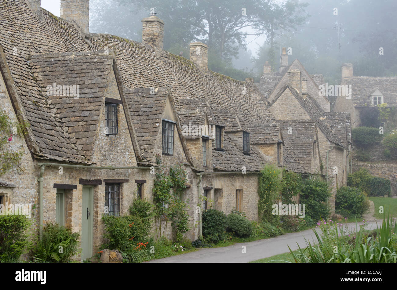 The Arlington Row, honey coloured weavers cottages in the morning fog in the town of Bibury in Gloucestershire in - Stock Image