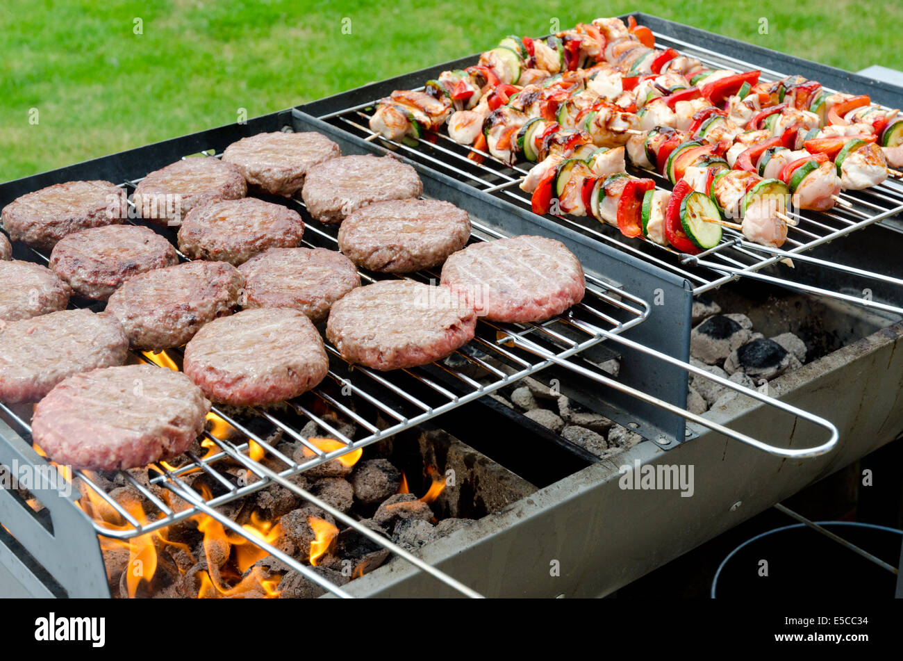 Charcoal Barbecue Bbq Loaded With Chicken Kebabs And Beef Burgers Stock Photo Alamy