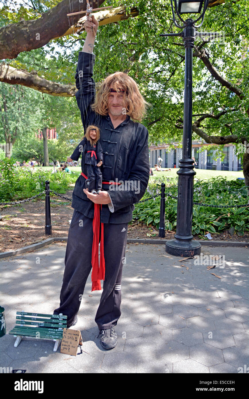 Portrait of Larry, an marionette puppeteer with his own mini-me puppet in Washington Square Park in NYC - Stock Image