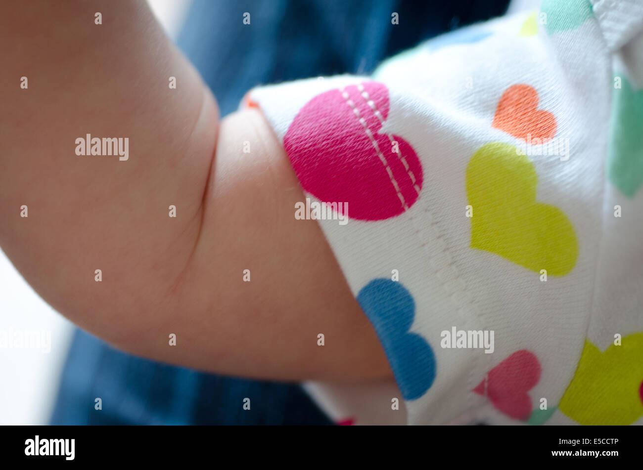 Baby girl three weeks old with arm biceps posed in babygro with heart motif - Stock Image
