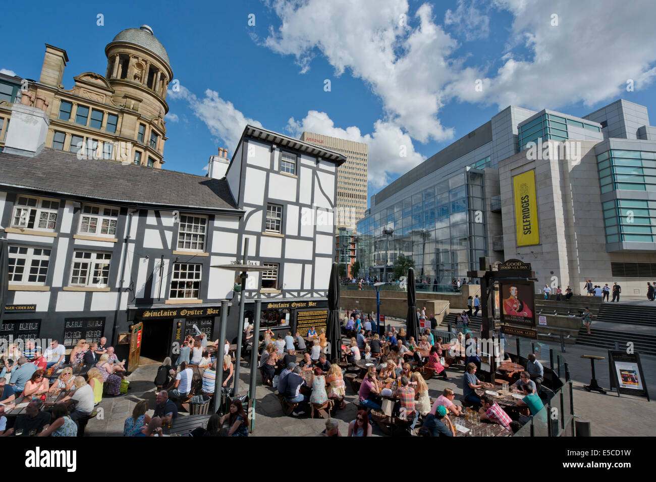 People enjoy themselves in beer garden of Sinclair's Oyster Bar near Corn Exchange Triangle in Manchester. - Stock Image