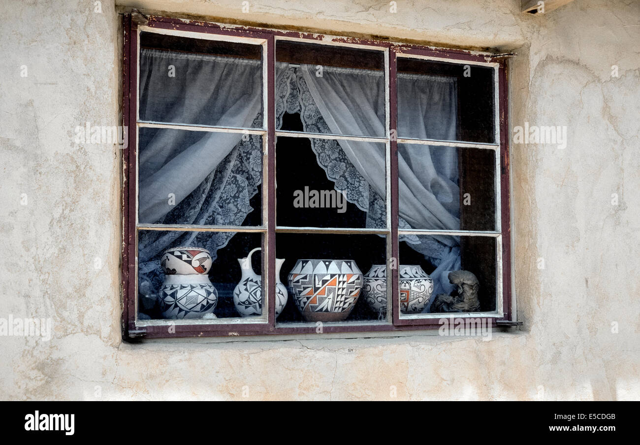 Seen in a window is Indian pottery waiting to be finished by Native American artisans in Acoma Pueblo, an indigenous - Stock Image