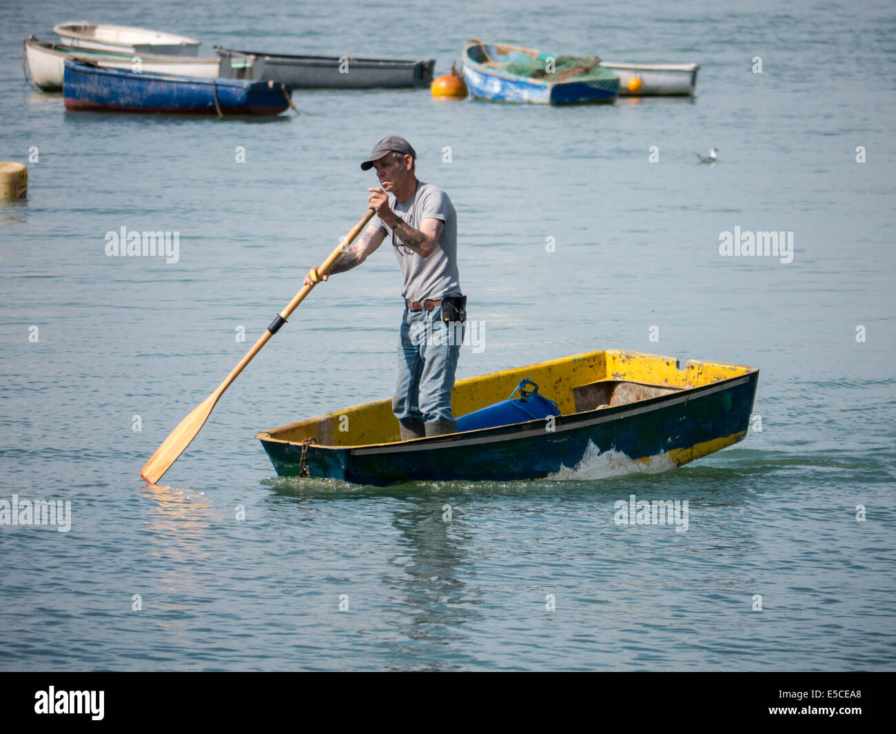 man standing in a boat rowing it to shore with one oar - Stock Image