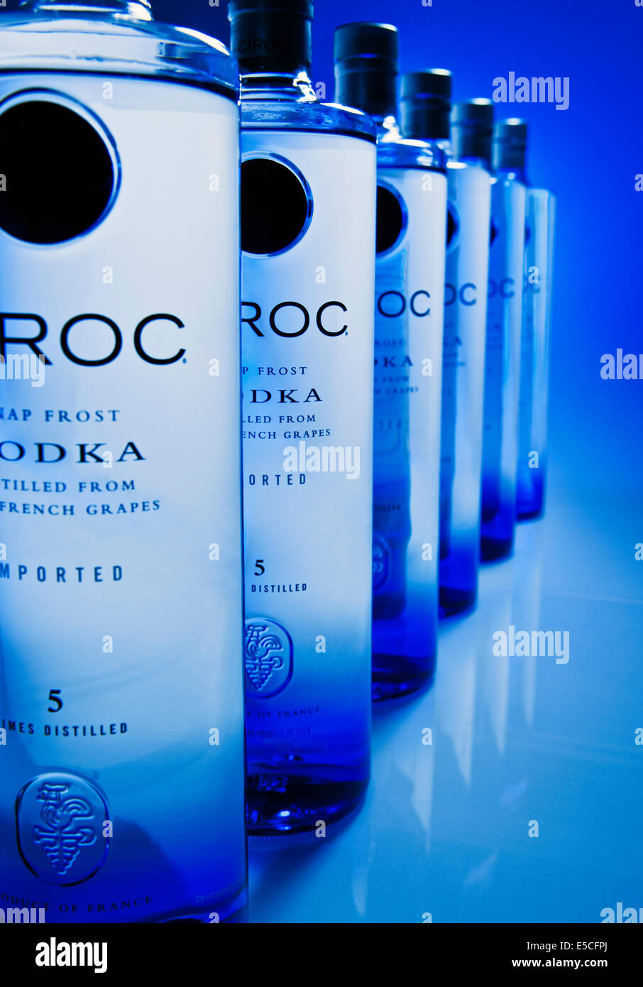 Ciroc Vodka bottles line up in perspective with a blue background - Stock Image