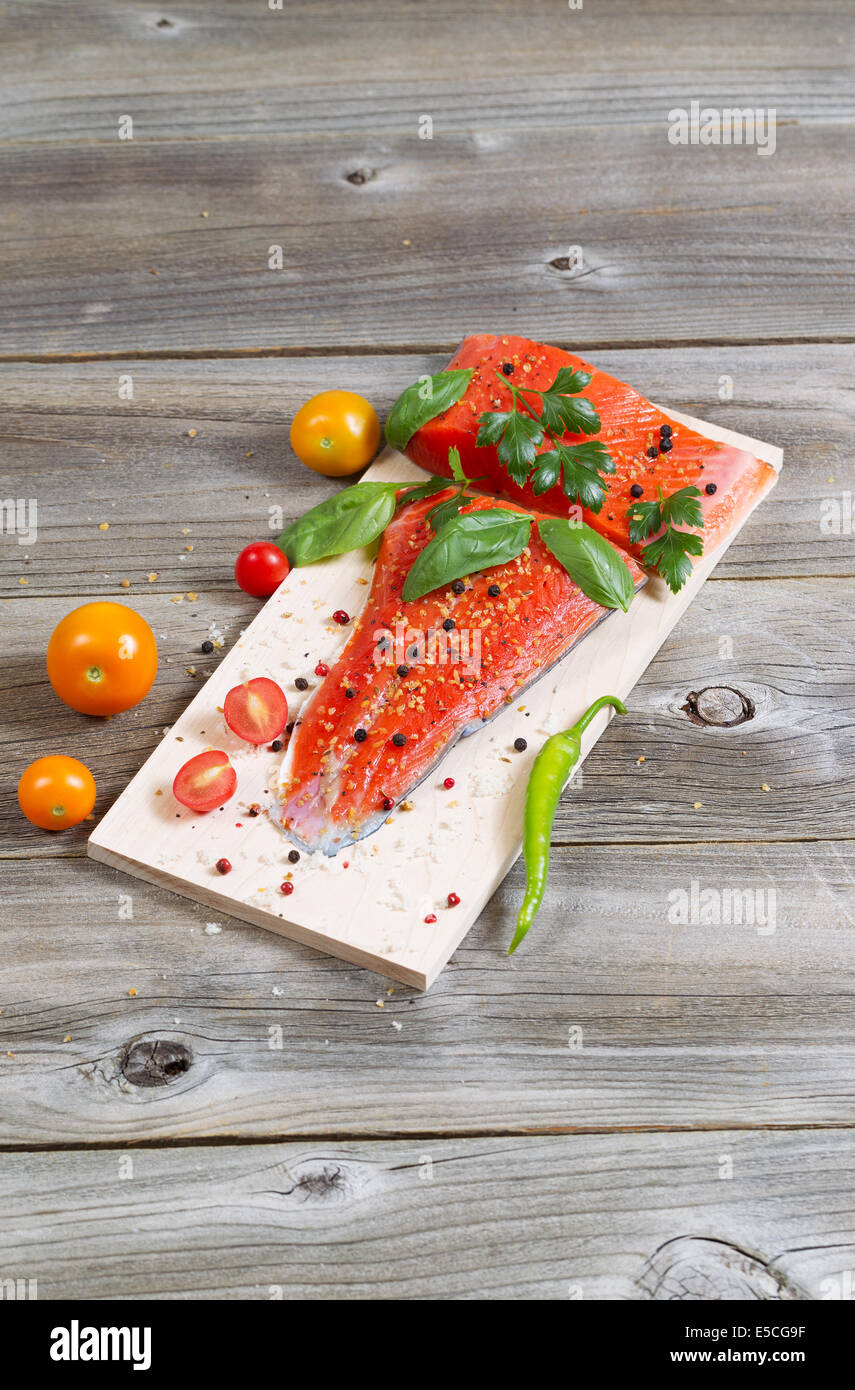 Vertical view of raw red salmon, skin side down, on maple wood grilling plank with seasoning and other herbs - Stock Image
