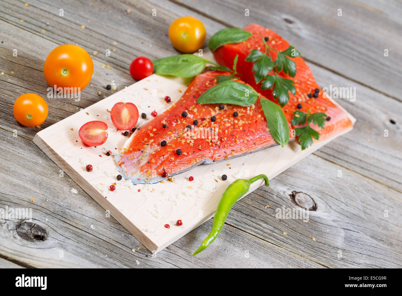 Angled horizontal view of raw red salmon, skin side down, on maple wood grilling plank with seasoning and other - Stock Image