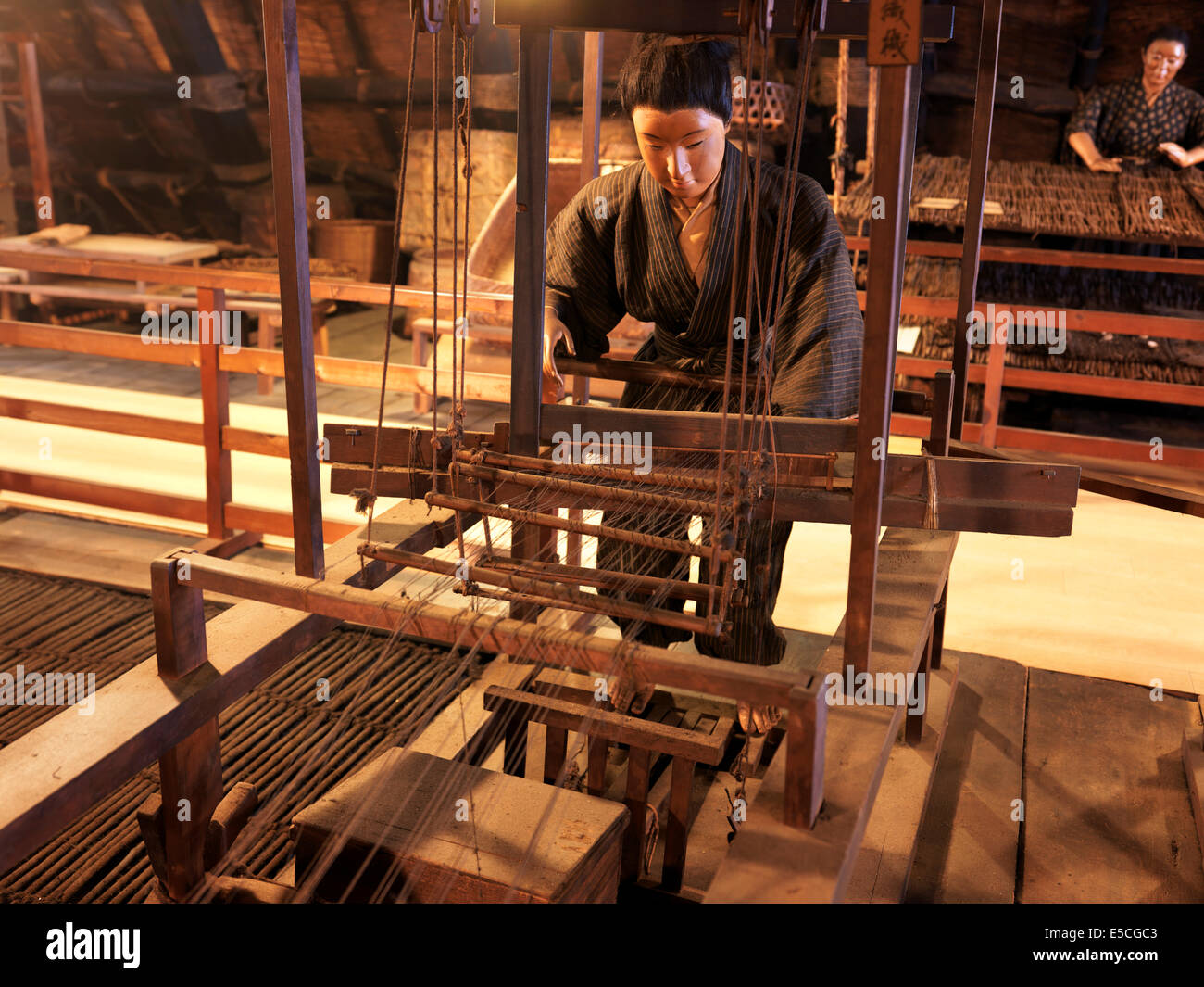 Japanese textile worker at an antique spinner machine. Museum display, Gero Onsen Gassho Village, Gifu Prefecture, - Stock Image