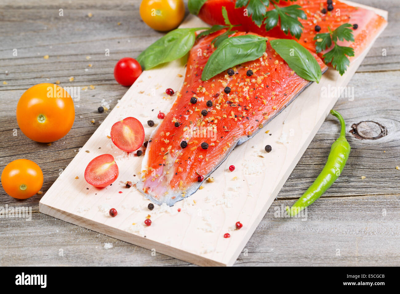 Closeup horizontal front view of raw red salmon, skin side down, on maple wood grilling plank with seasoning and - Stock Image