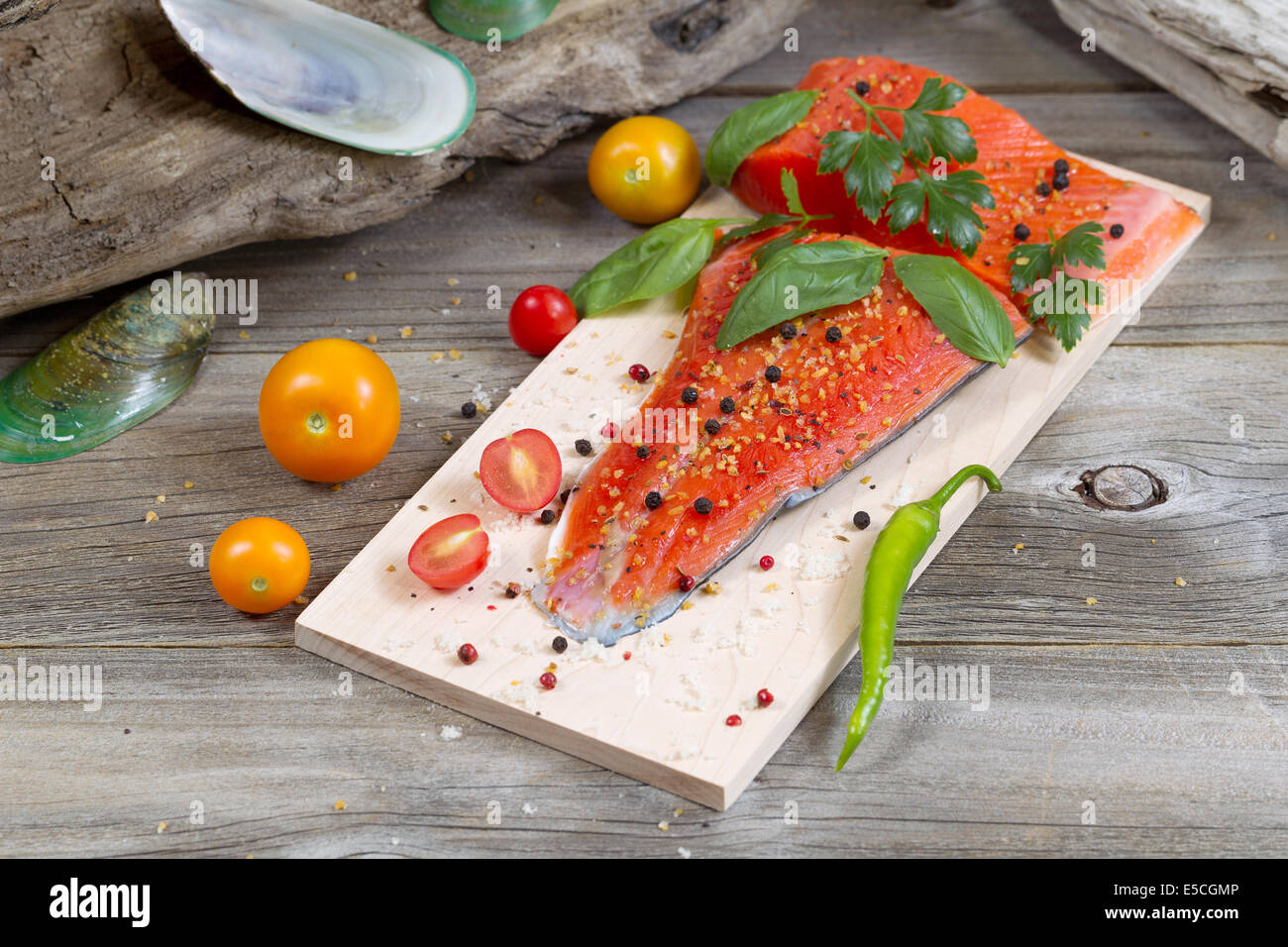 Horizontal view of raw red salmon, skin side down, on maple wood grilling plank with seasoning and other herbs - Stock Image
