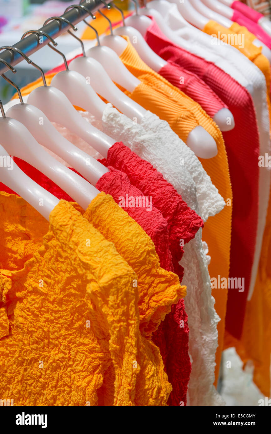 Colorful womens tops on clothes hangers in a store in Japan - Stock Image