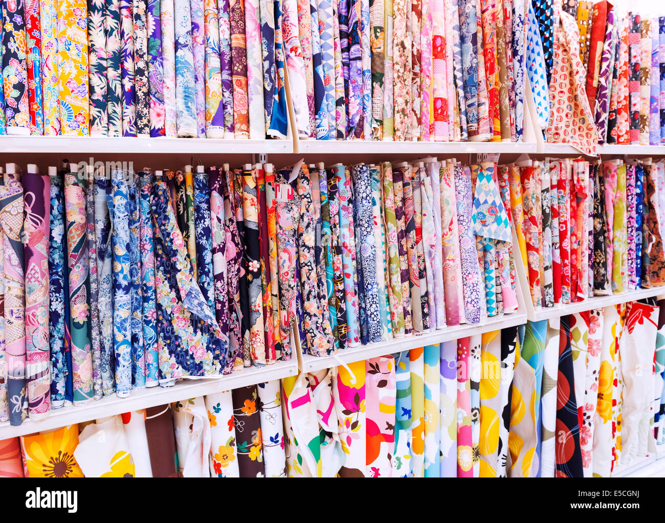 Textiles with colorful patterns on display in a fabric store in Japan - Stock Image