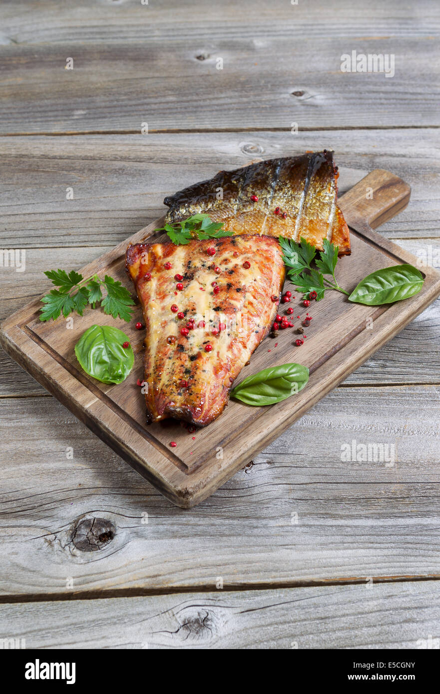 Vertical view of smoked salmon fillets, fresh out of cooker, with seasoning on serving board with rustic wood underneath - Stock Image