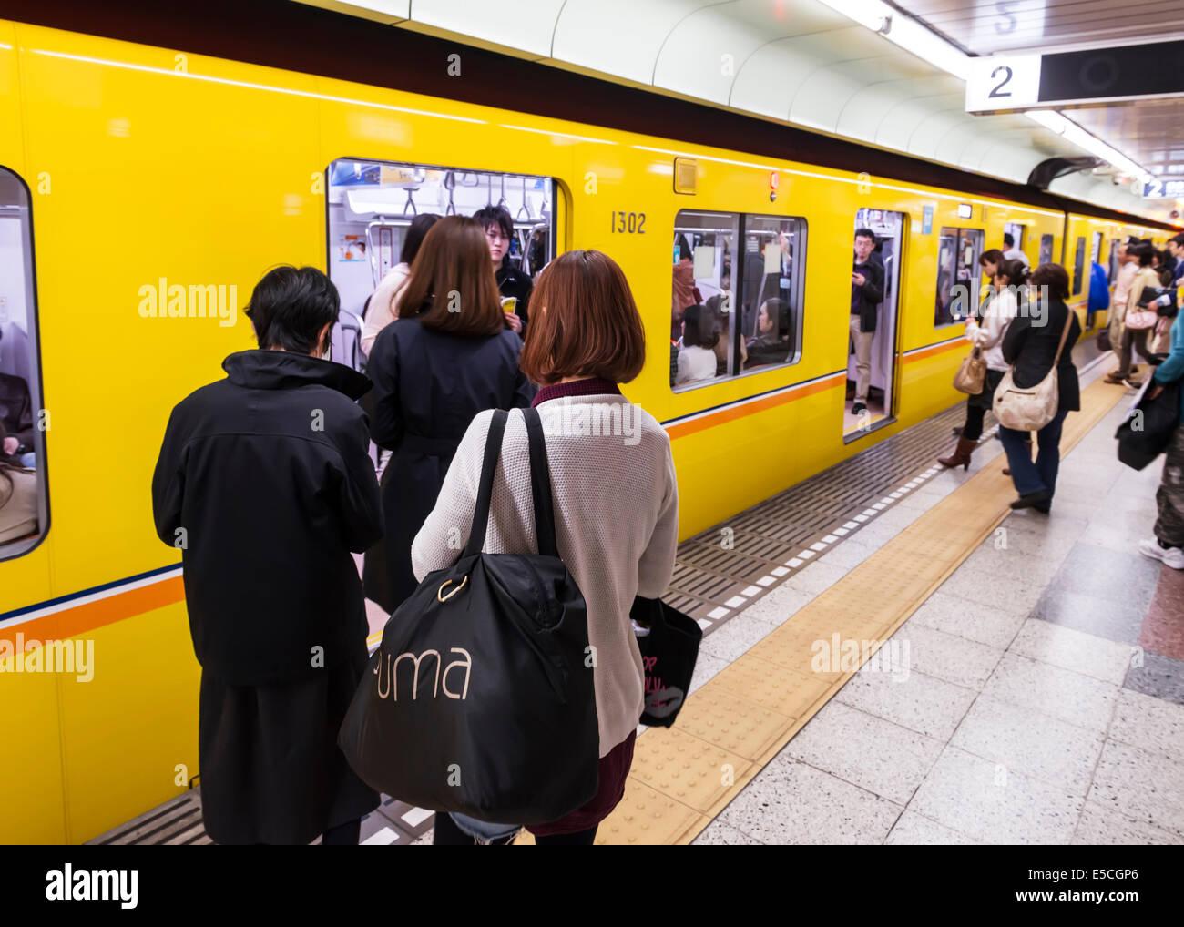 People at a subway station platform entering a train. Tokyo Metro, Tokyo, Japan. Stock Photo