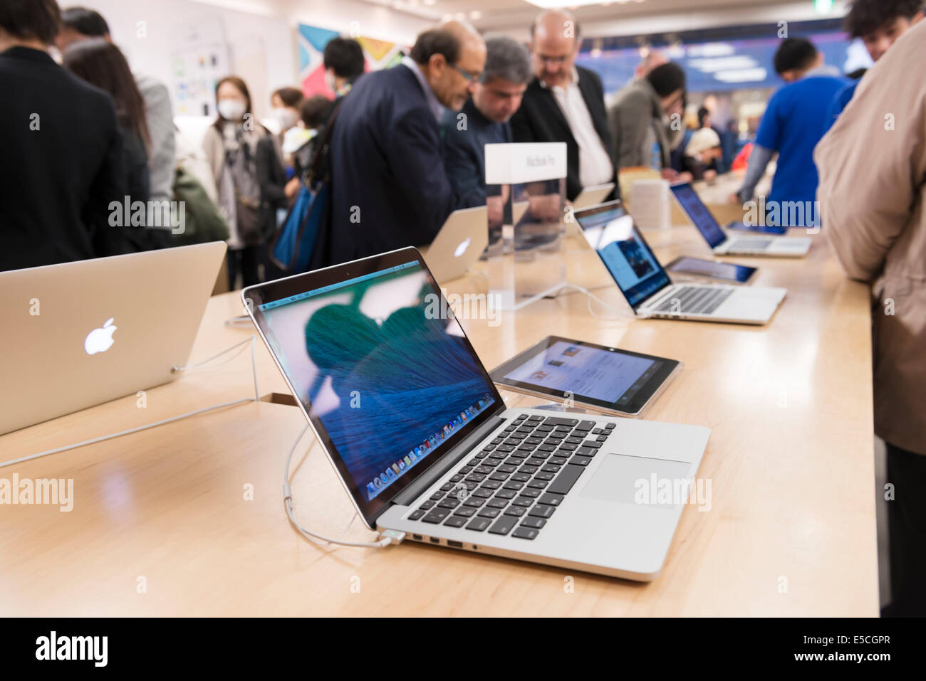People at Apple store trying new MacBooks laptop computers. Ginza, Tokyo, Japan 2014 - Stock Image