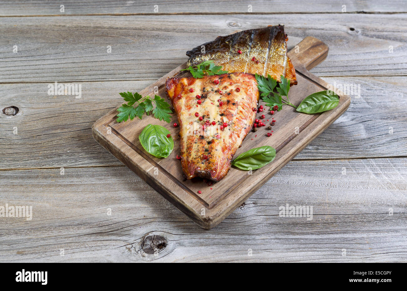 Horizontal view of smoked salmon fillets, fresh out of cooker, with seasoning on serving board with rustic wood - Stock Image