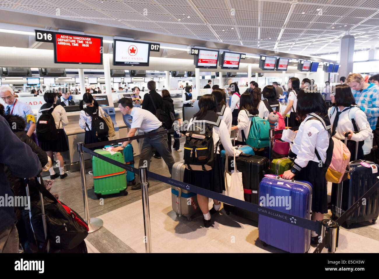 Japanese schoolgirls lined up at Air Canada check-in counter of Narita International Airport in Japan - Stock Image