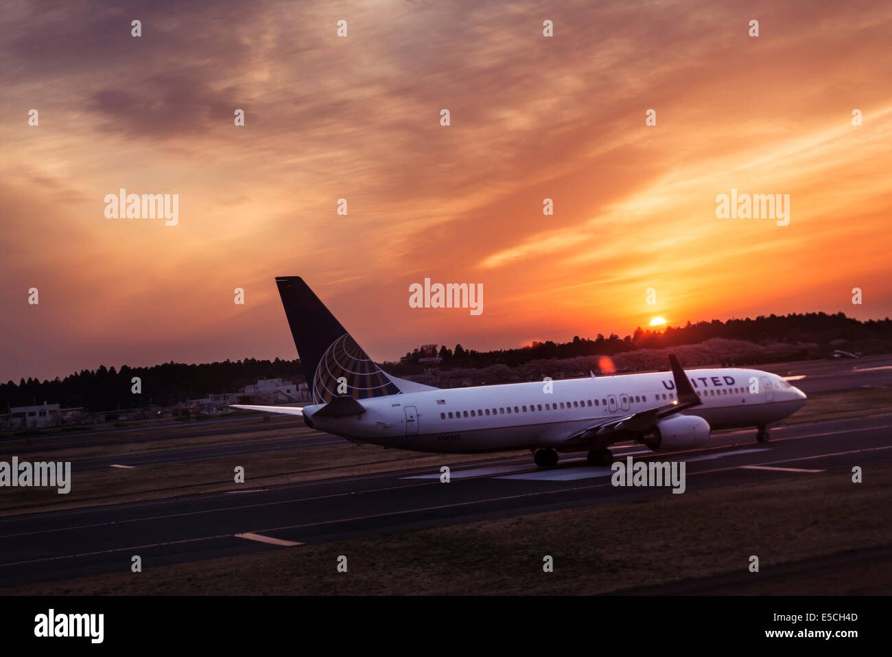 United Airlines airplane taking off on a runway at Narita International airport during sunset. Japan. - Stock Image