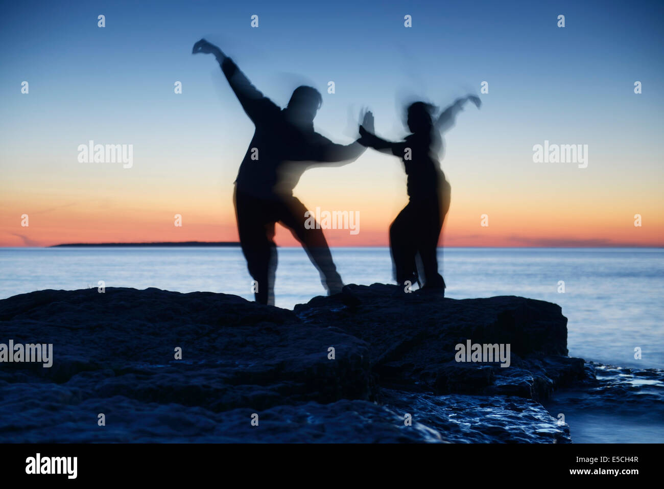 Two blurred silhouettes of people practicing martial arts at dusk in the nature over colorful twilight sky - Stock Image