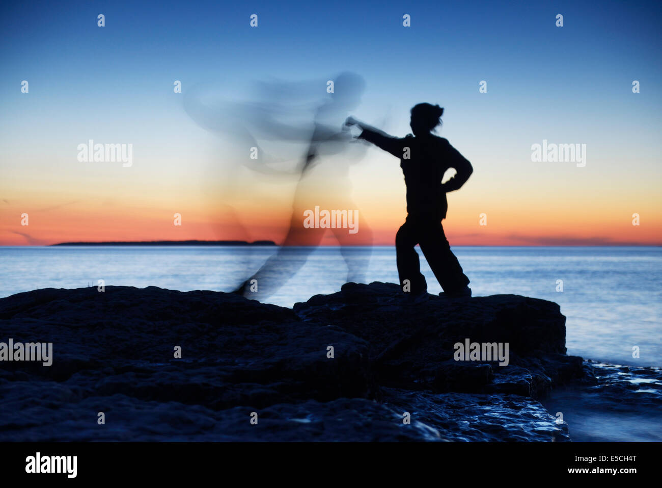Woman attacking a ghost shadow of a man blurred silhouette over colorful twilight sky - Stock Image