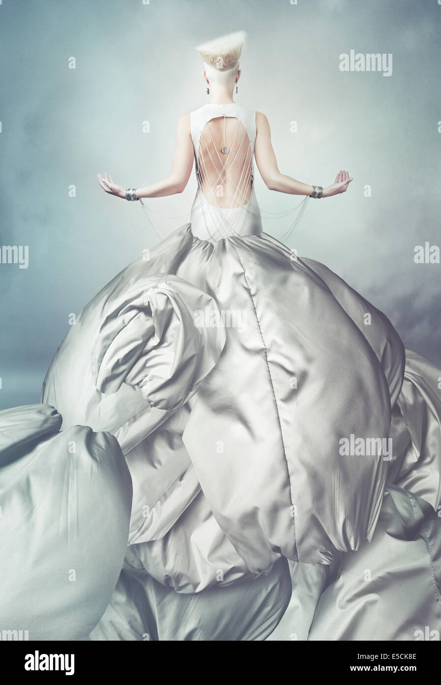 blond woman in big grey dress with creative hairstyle Stock Photo