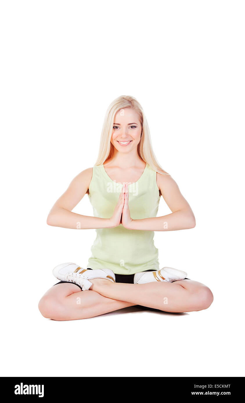 blonde girl siting in yoga pose on white background - Stock Image