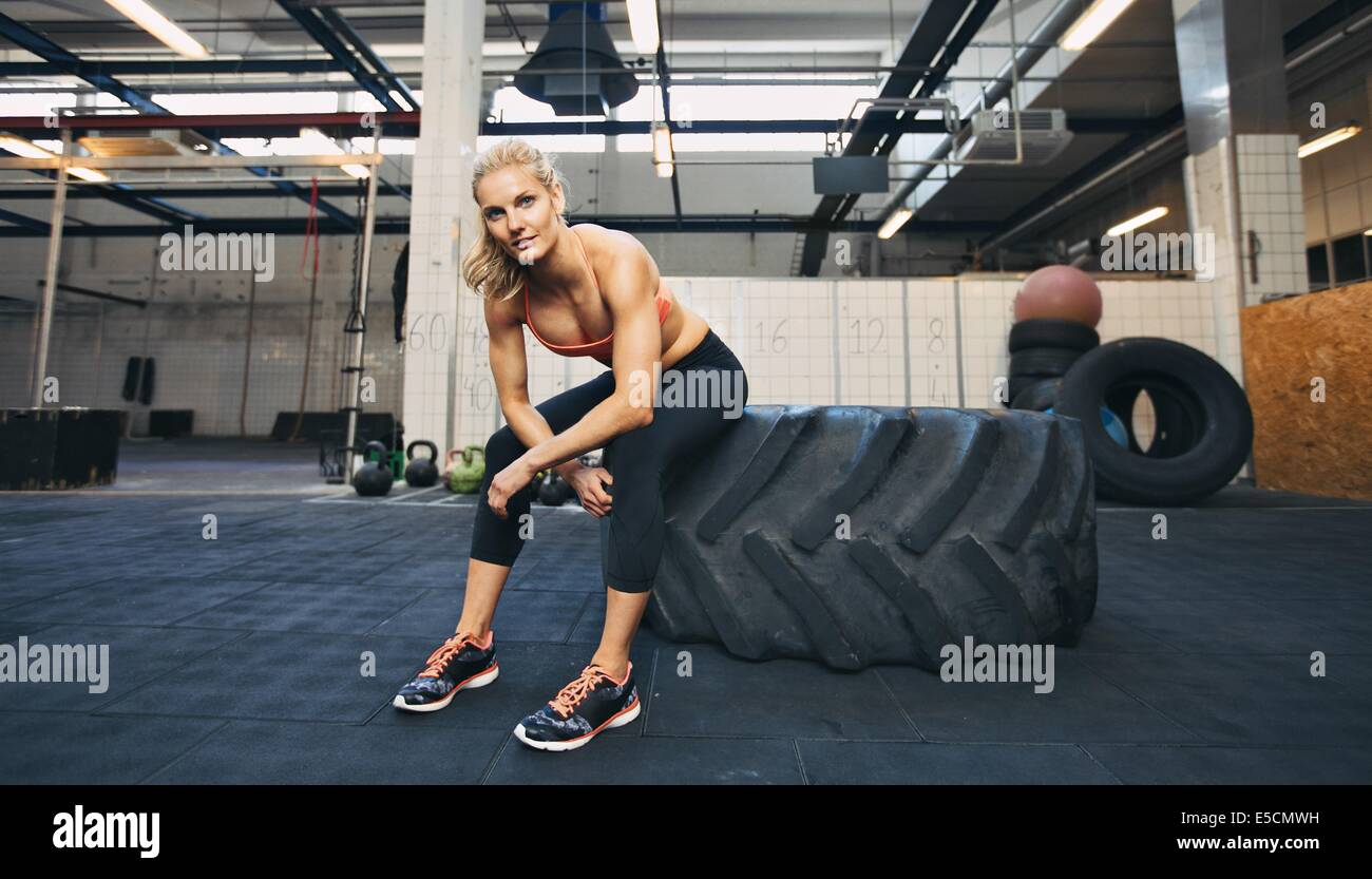Beautiful and strong young woman sitting on a big tire after her exercise. Woman taking break after crossfit workout - Stock Image