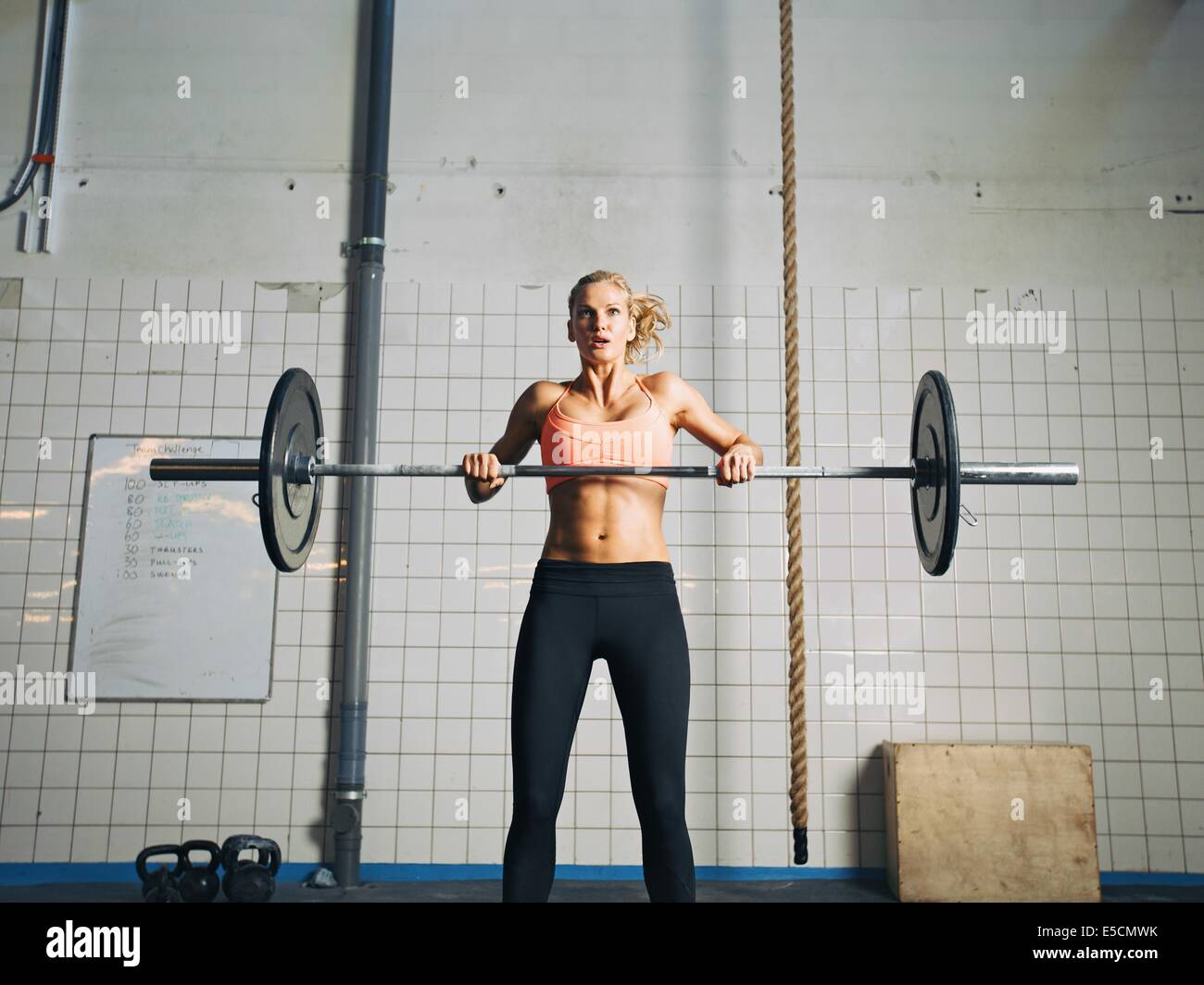 Young strong woman practices cross fit in a gym. Fit female holding a barbell with weights for crossfit. - Stock Image