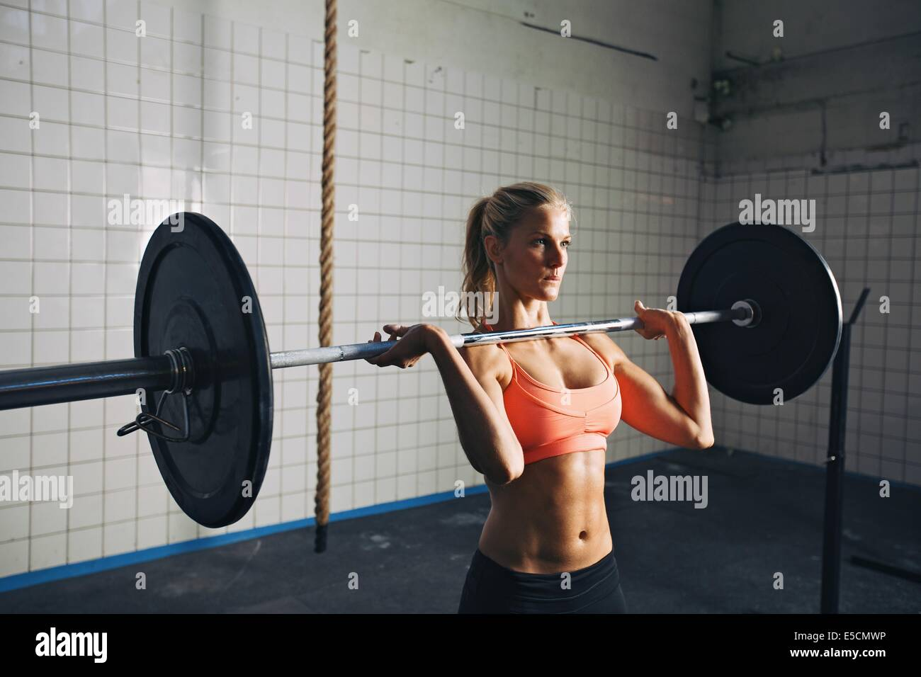 Fitness woman concentrating while lifting barbells. Strong woman lifting weights in crossfit gym. Caucasian female - Stock Image