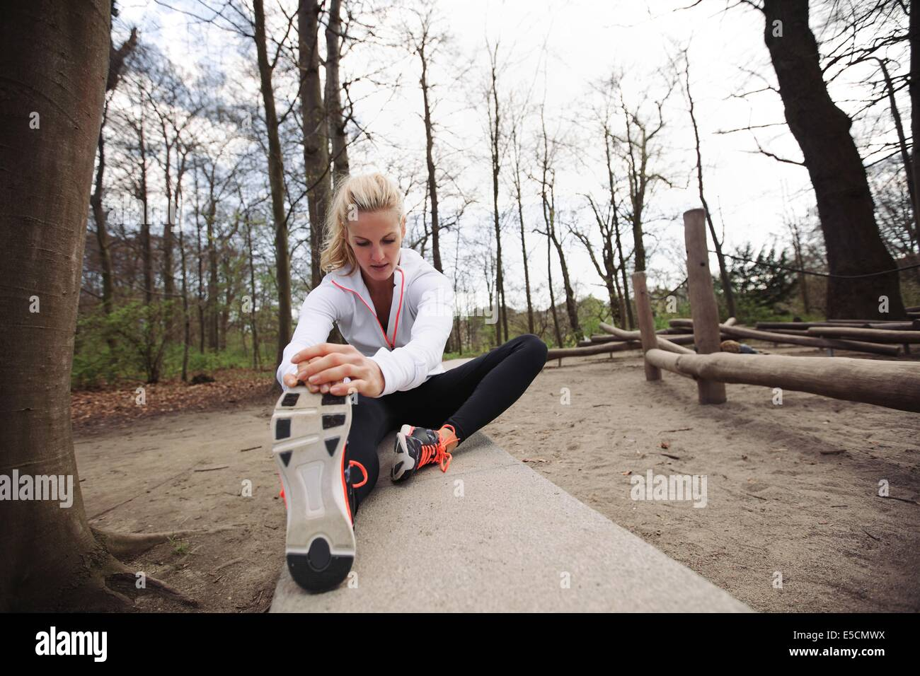 Fit woman stretching her legs before a run. Caucasian female model exercising in park. - Stock Image