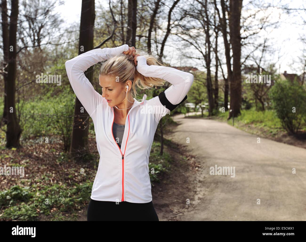 Fit female athlete tying hair before her run. Pretty young woman preparing for her run in forest. - Stock Image