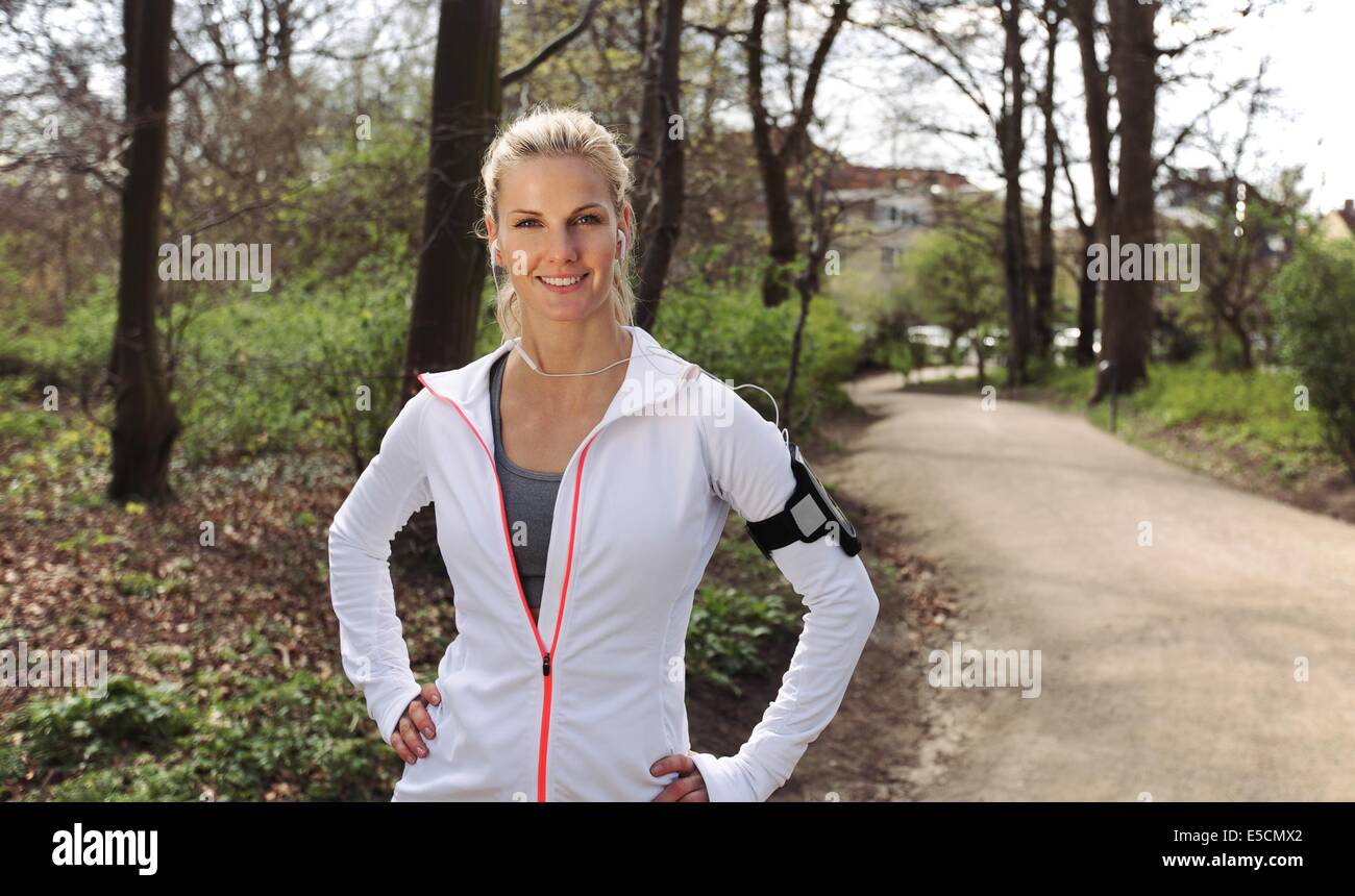 Beautiful and confident young fitness woman outdoors. Caucasian female runner out in forest for training. - Stock Image