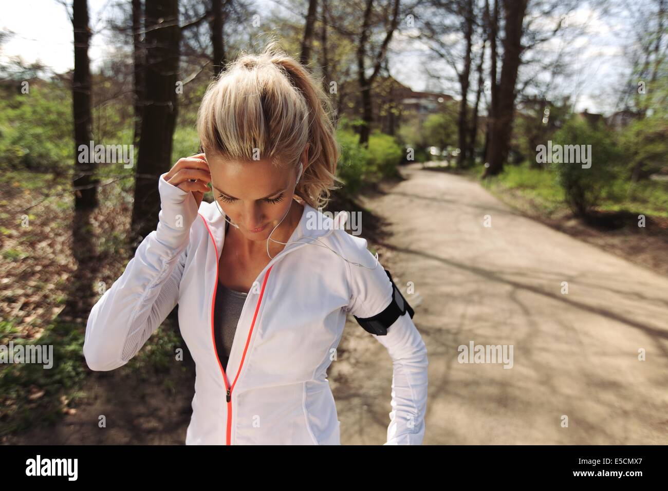 Image of pretty young blonde wearing earphones to listen music before starting her running workout. Fit female athlete Stock Photo