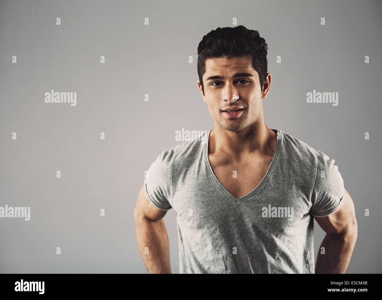 Portrait of confident young hispanic male fashion model posing against grey background with copy space. - Stock Image