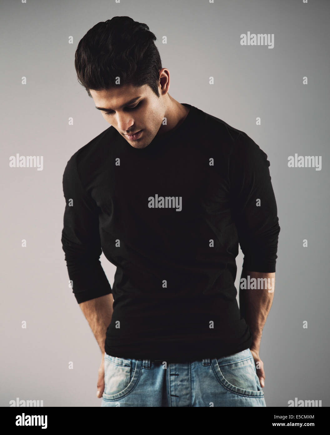 Portrait of hispanic young man standing on grey background looking down thinking. - Stock Image