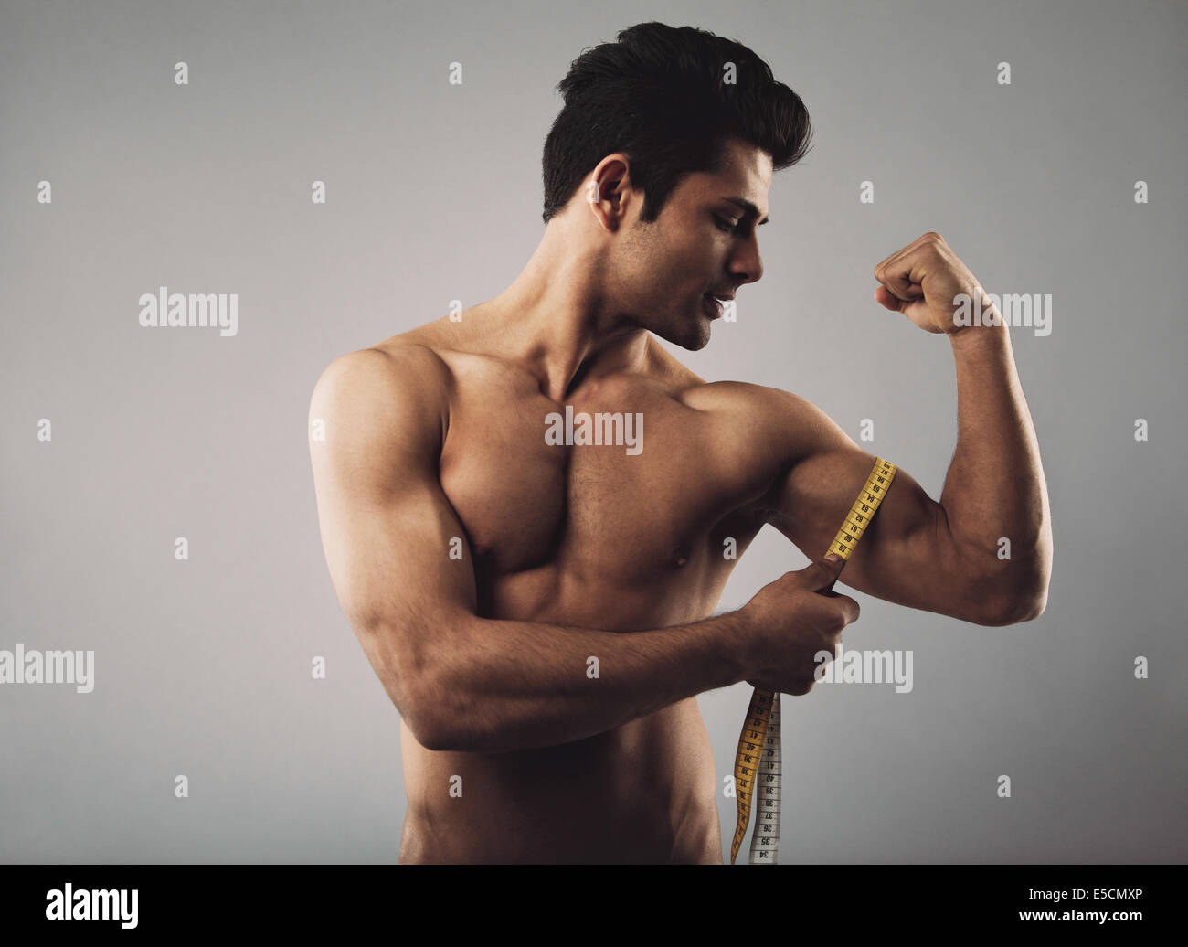 Fitness man measuring his body. Muscular male measuring biceps by tape measure isolated on grey background. - Stock Image