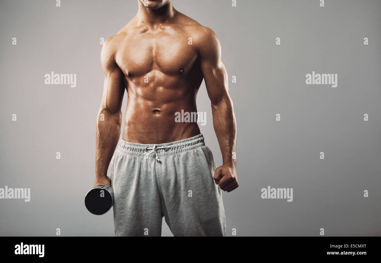Cropped image of young muscular male fitness model wearing sweatpants holding a dumbbell against grey background. Stock Photo