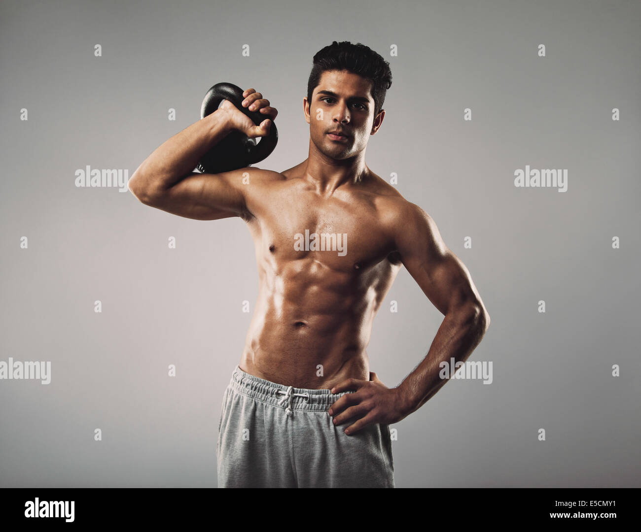 Handsome young muscular man holding kettle bell in studio. Hispanic fitness male model working out with kettlebell - Stock Image